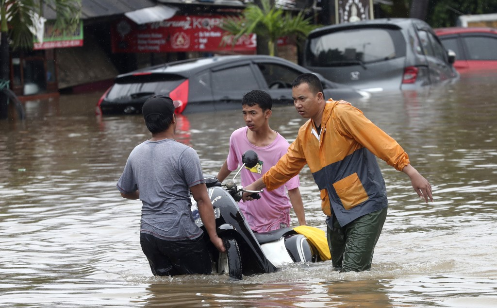 Indonesian people wade through floodwaters at Jatibening on the outskirt of Jakarta, Indonesia, Wednesday, Jan. 1, 2020. Severe flooding hit Indonesia...