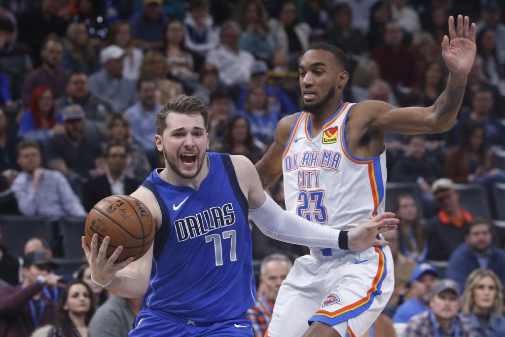Dallas Mavericks forward Luka Doncic (77) drives past Oklahoma City Thunder guard Terrance Ferguson (23) during the first half of an NBA basketball ga...