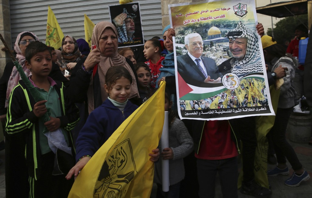 Palestinian Fatah supporters hold portraits of Palestinian President Mahmoud Abbas and late Palestinian President Yasser Arafat during a celebration m...