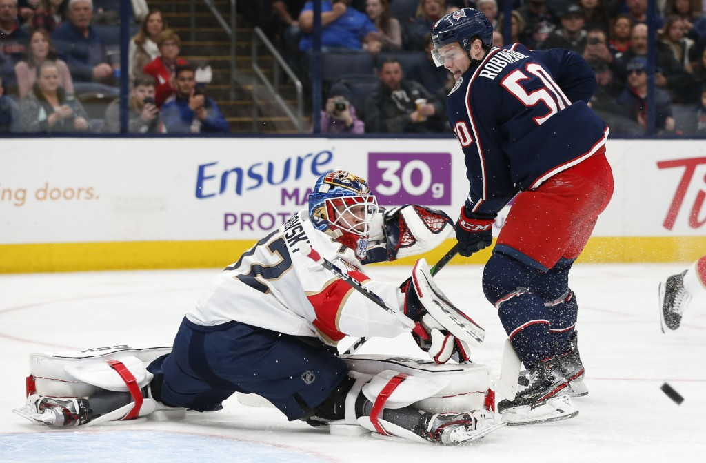 Florida Panthers' Sergei Bobrovsky, left, of Russia, makes a save against Columbus Blue Jackets' Eric Robinson during the second period of an NHL hock...