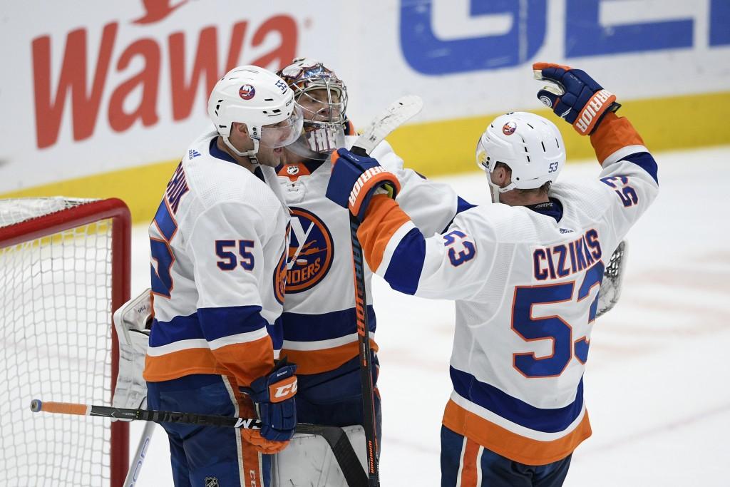 New York Islanders center Casey Cizikas (53), defenseman Johnny Boychuk (55) and goaltender Semyon Varlamov (40) celebrate after an NHL hockey game ag...
