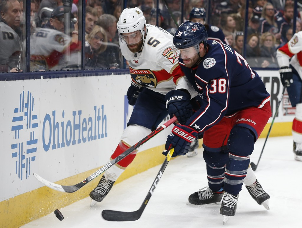 Florida Panthers' Aaron Ekblad, left, and Columbus Blue Jackets' Boone Jenner compete for the puck during the second period of an NHL hockey game Tues...