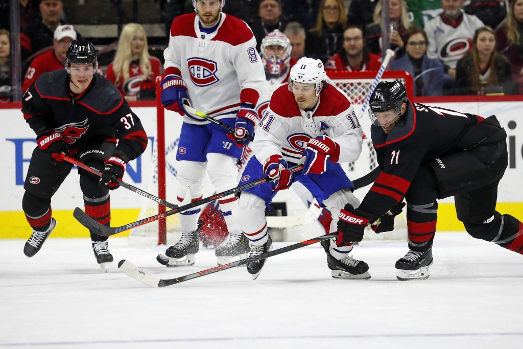 Carolina Hurricanes' Jordan Staal (11) battles with Montreal Canadiens' Brendan Gallagher (11) as Carolina Hurricanes' Andrei Svechnikov (37), of Russ...