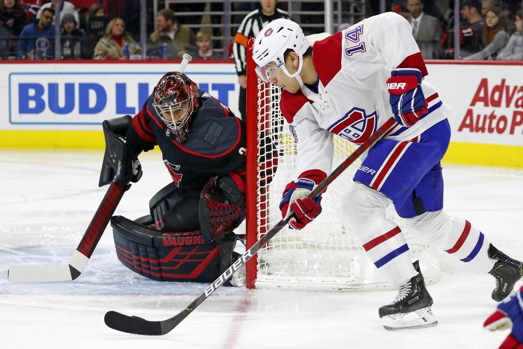 Montreal Canadiens' Nick Suzuki (14) moves the puck around the net to challenge Carolina Hurricanes goaltender Petr Mrazek (34), of Czech Republic, du...
