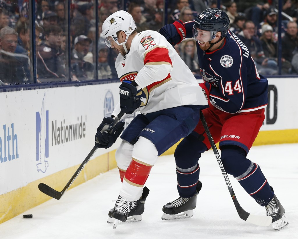 Florida Panthers' Colton Sceviour, left, and Columbus Blue Jackets' Vladislav Gavrikov, of Russia, vie for the puck during the first period of an NHL ...