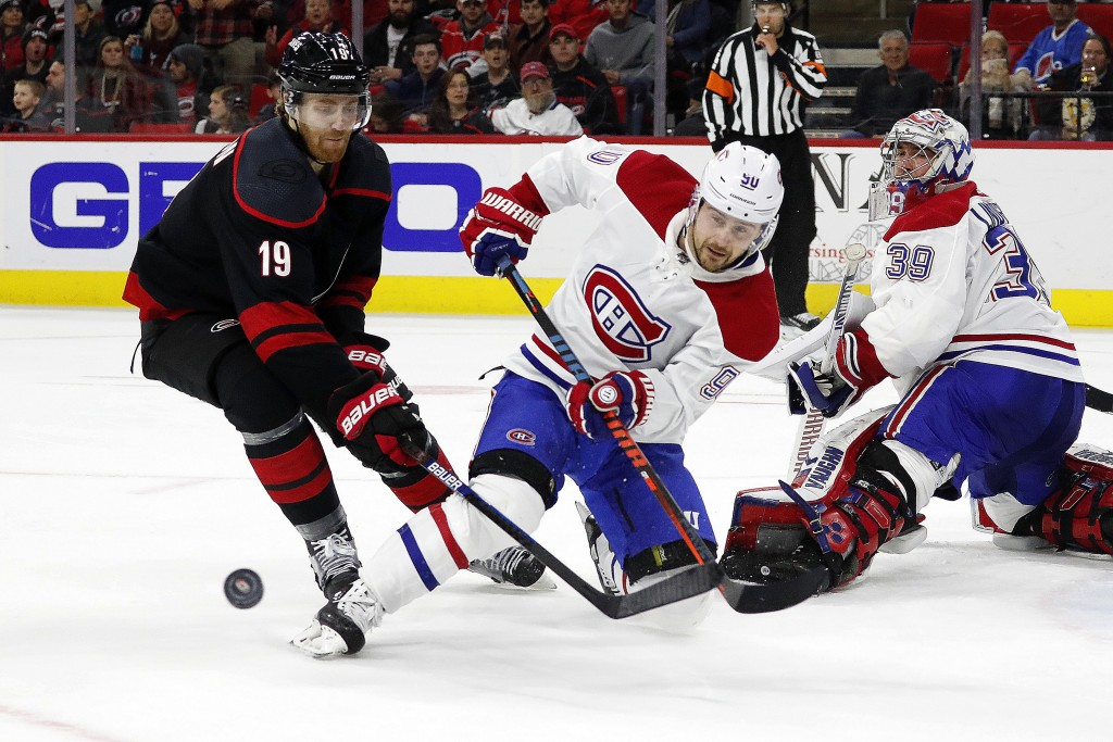 Montreal Canadiens' Tomas Tatar (90), of Slovakia, clears the puck in front of Carolina Hurricanes' Dougie Hamilton (19) during the second period of a...