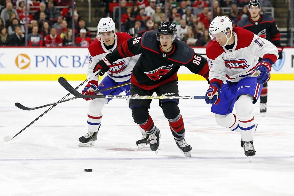 Carolina Hurricanes' Teuvo Teravainen (86), of Finland, battles between Montreal Canadiens' Nick Suzuki (14) and Brett Kulak (17) during the second pe...