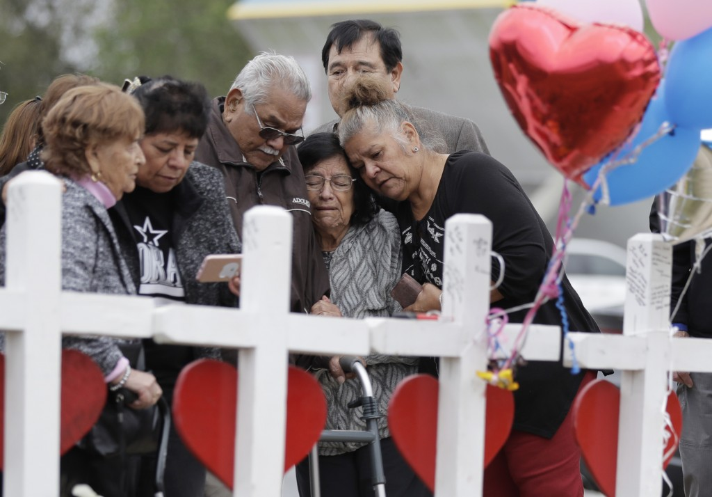 FILE - In this Nov. 10, 2017, file photo, family and friends gather around a makeshift memorial for the victims of the First Baptist Church shooting a...