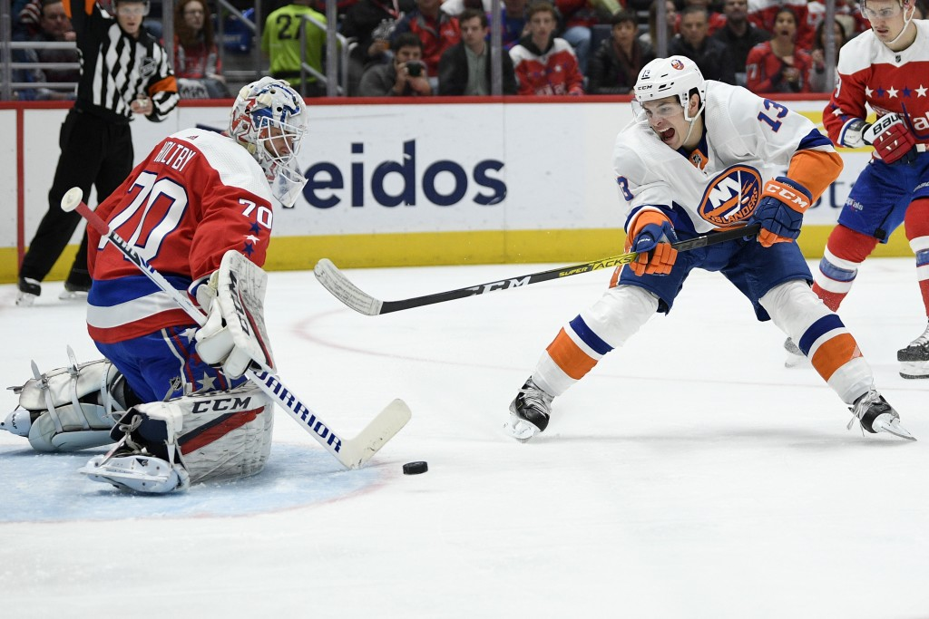 Washington Capitals goaltender Braden Holtby (70) reaches out for a shot by New York Islanders center Mathew Barzal (13) during the first period of an...