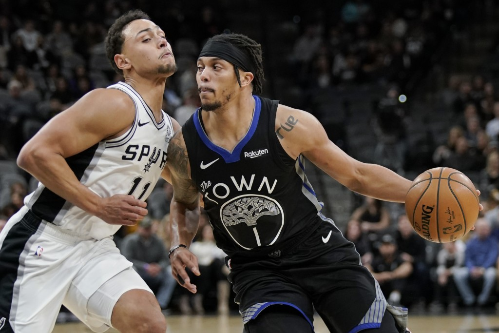 Golden State Warriors' Damion Lee (1) drives against San Antonio Spurs' Bryn Forbes during the first half of an NBA basketball game, Tuesday, Dec. 31,...