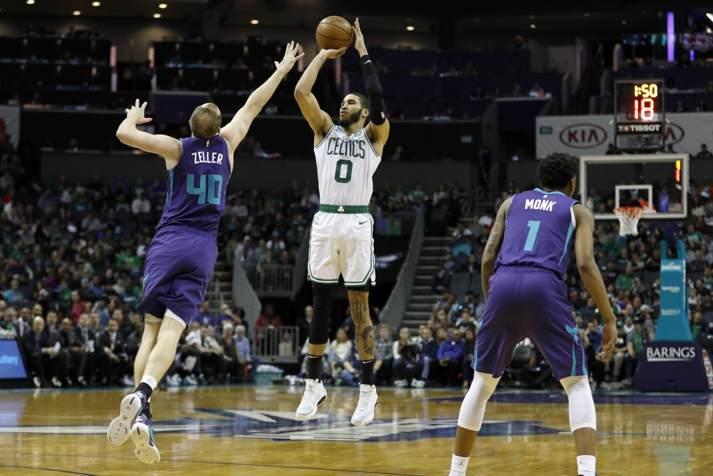 Boston Celtics' Jayson Tatum (0) aims a three-pointer as Charlotte Hornets' Cody Zeller (40) stretches to defend during the first half of an NBA baske...