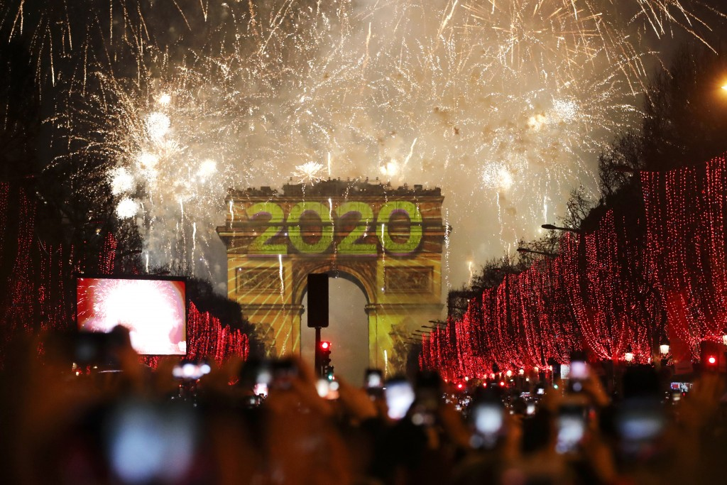 Revellers photograph fireworks over the Arc de Triomphe as they celebrate the New Year on the Champs Elysees, in Paris, France, Wednesday, Jan. 1, 202...