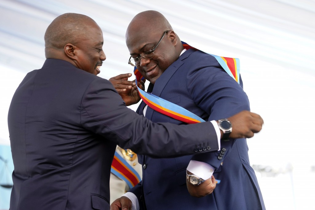 FILE - In this Thursday Jan. 24, 2019 file photo, Congolese President Felix Tshisekedi, right, receives the presidential sash from outgoing president ...
