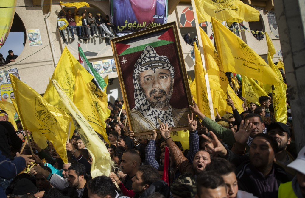 A Palestinian carries a picture of the late Palestinian leader Yasser Arafat, during a rally marking the 55th anniversary of the Fatah movement foundi...