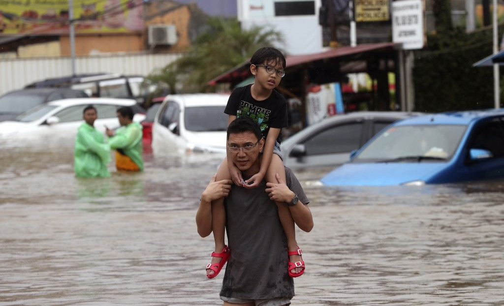A man carrying a boy wades through floodwaters at Jatibening on the outskirt of Jakarta, Indonesia, Wednesday, Jan. 1, 2020. Severe flooding hit Indon...