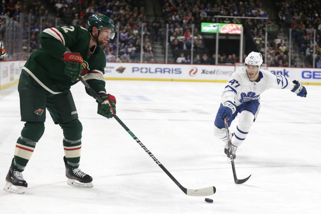Minnesota Wild center Eric Staal (12) controls the puck in front of Toronto Maple Leafs left wing Pierre Engvall (47) and Maple Leafs center Auston Ma...