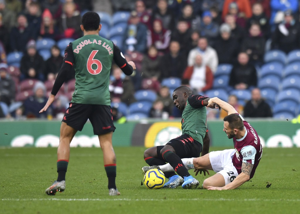 Aston Villa's Marvelous Nakamba, centre is tackled by Burnley's Phil Bardsley, during the English Premier League soccer match between Burnley and Asto...