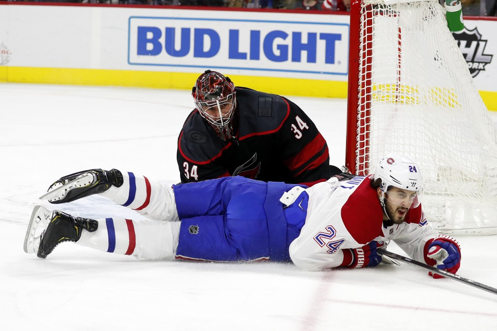 Montreal Canadiens' Phillip Danault (24) slides on the ice past Carolina Hurricanes goaltender Petr Mrazek (34), of the Czech Republic, during the fir...