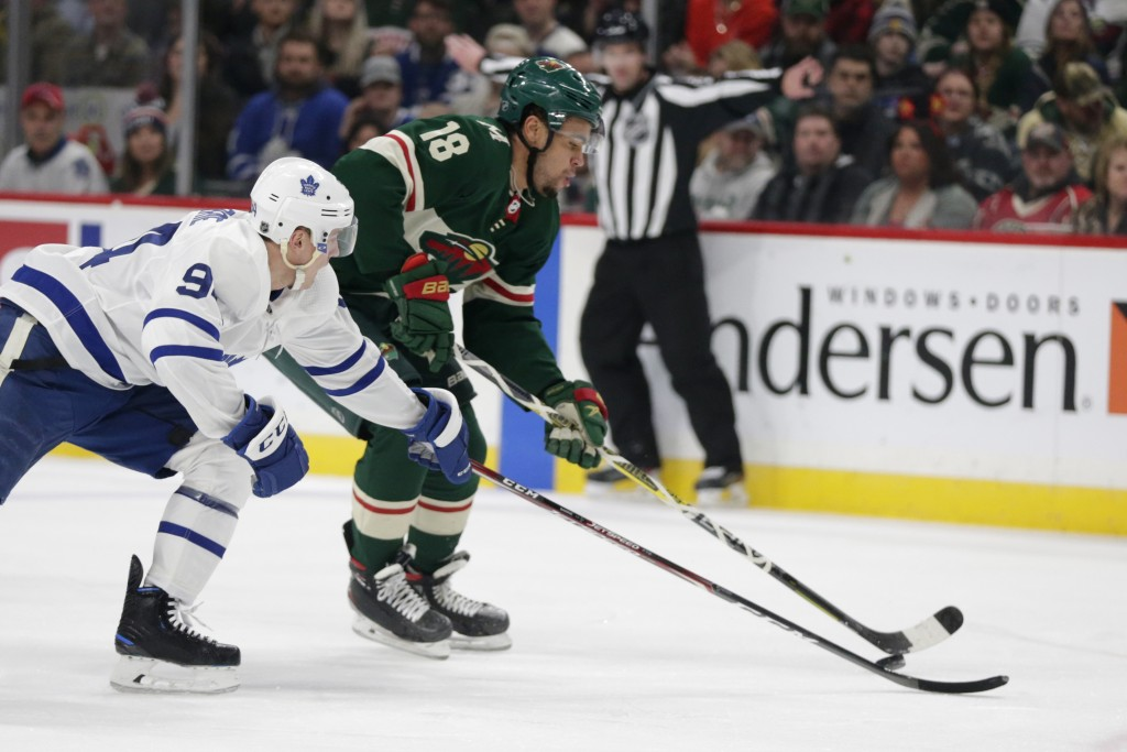 Minnesota Wild left wing Jordan Greenway (18) controls the puck in front of Toronto Maple Leafs center Jason Spezza (19) and Maple Leafs center Auston...