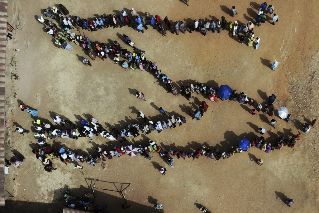 FILE - In this Saturday, Feb. 23, 2019 file photo, Nigerians line up to cast their votes in the presidential election at the Narayi primary school in ...