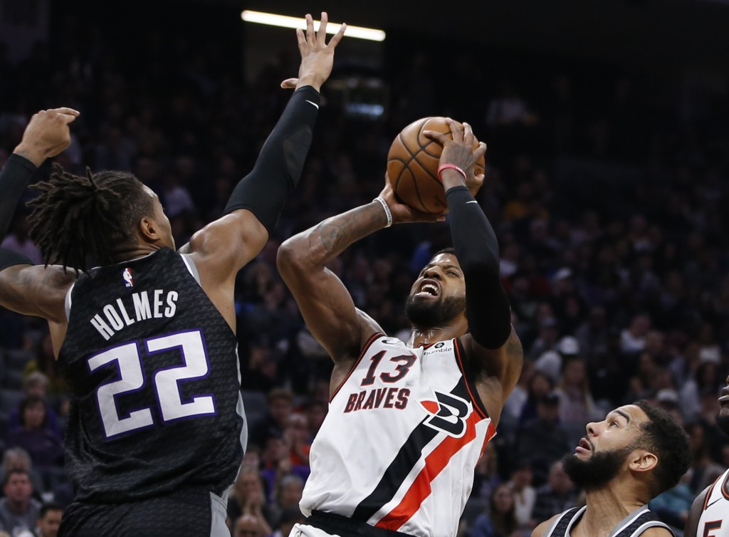 Los Angeles Clippers forward Paul George, center, goes up for a shot between Sacramento Kings' Richaun Holmes, left, and Cory Joseph, right, during th...