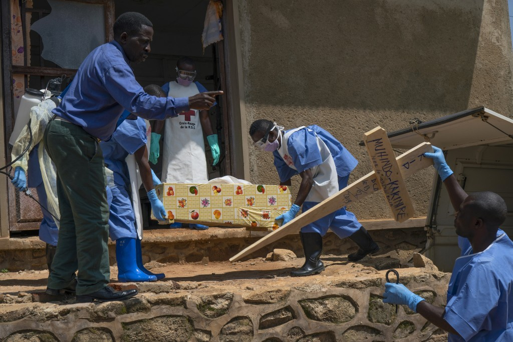 FILE - In this Sunday, July 14, 2019 file photo, Red Cross workers carry the remains of 16-month-old Muhindo Kakinire from the morgue into a truck as ...