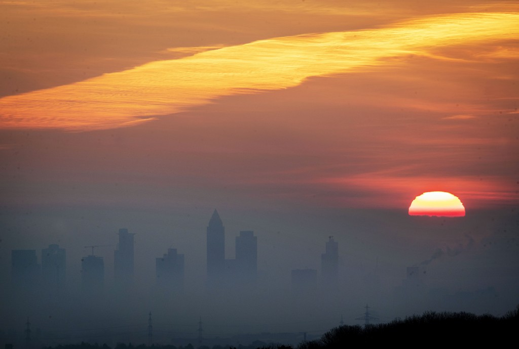 The sun rises over the buildings of the banking district in Frankfurt, Germany, on a misty Wednesday, Jan. 1, 2020. (AP Photo/Michael Probst)