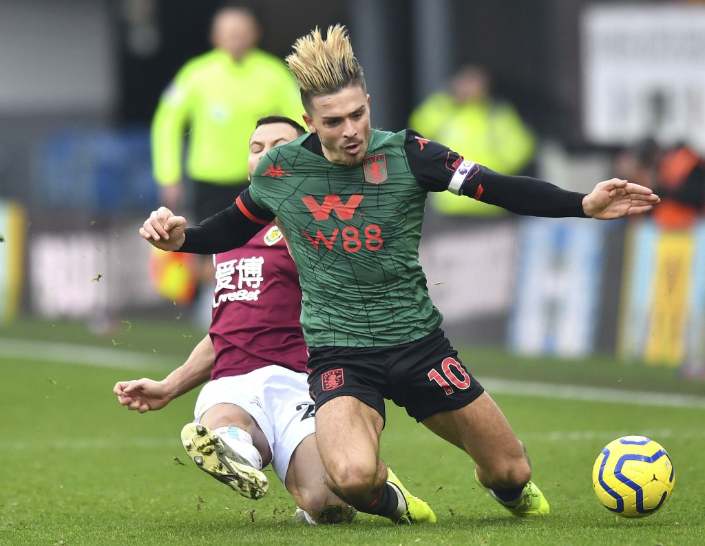 Burnley's Phil Bardsley, background tackles Aston Villa's Jack Grealish, during the English Premier League soccer match between Burnley and Aston Vill...