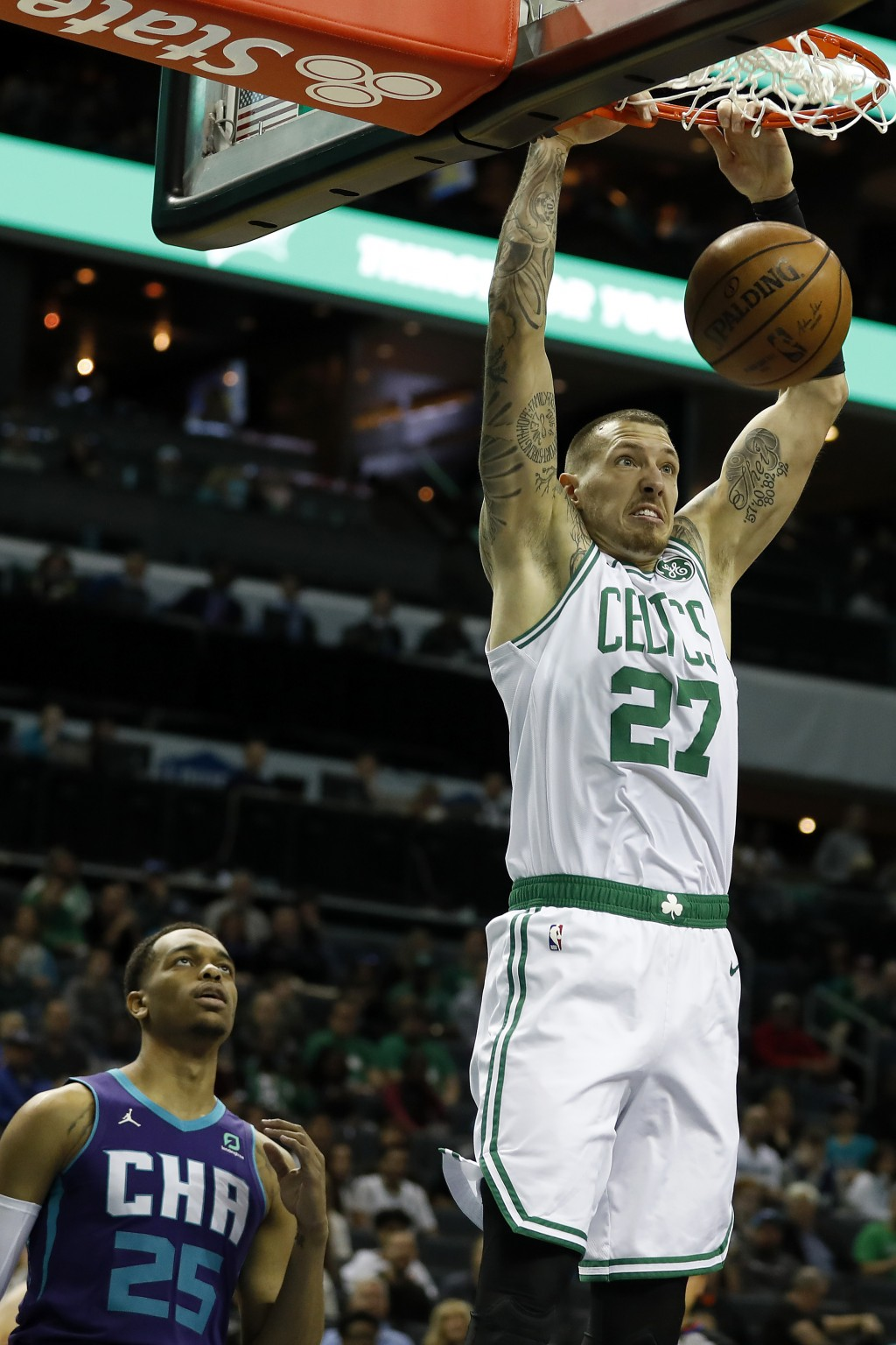 Boston Celtics' Daniel Theis (27) dunks as Charlotte Hornets' P.J. Washington (25) can only watch during the first half of an NBA basketball game in C...