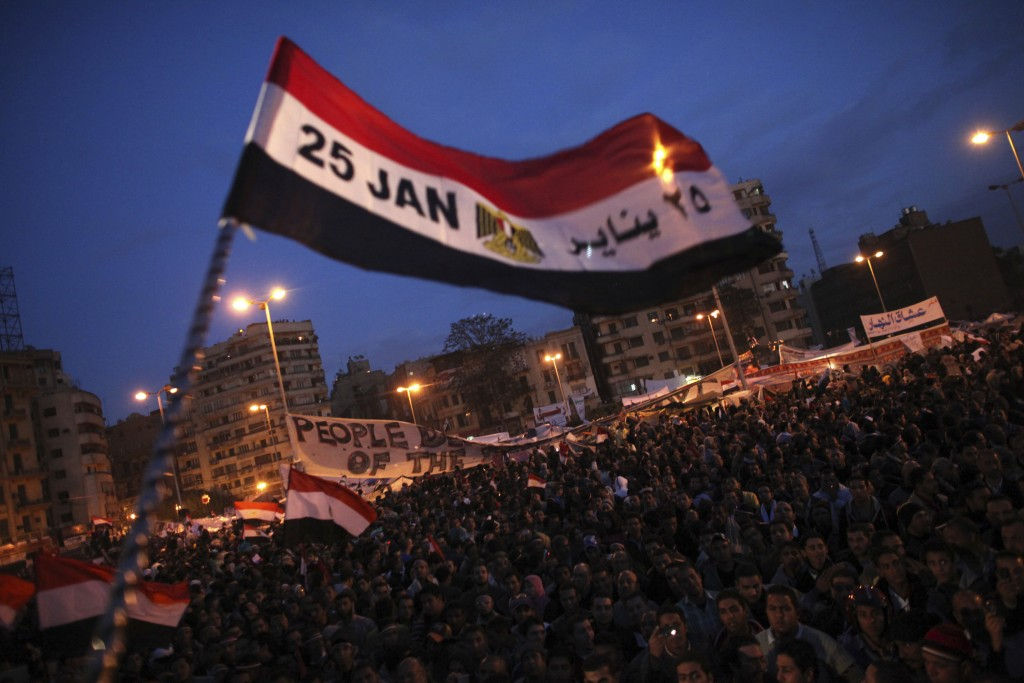 FILE -- In this Feb. 10, 2011 file photo, a flag is waved by anti-government protesters as they demonstrate in Tahrir Square in downtown Cairo, Egypt....