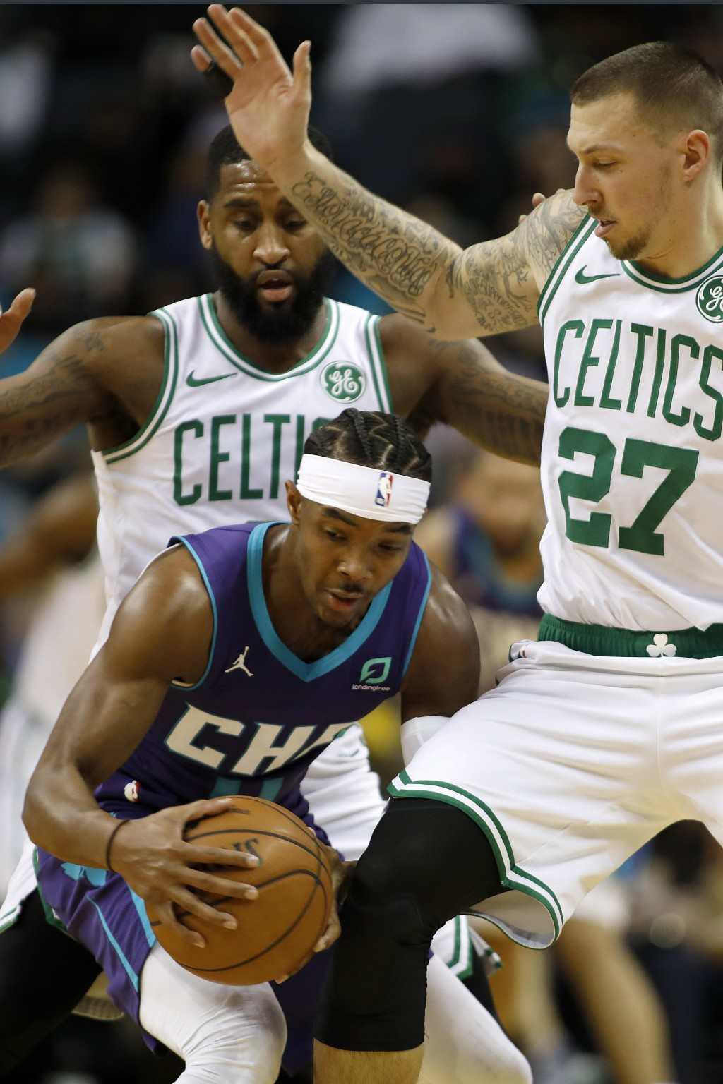 Charlotte Hornets' Devonte' Graham (4) tries to hold possession as he is double teamed by Boston Celtics' Brad Wanamaker, back and Daniel Theis (27), ...