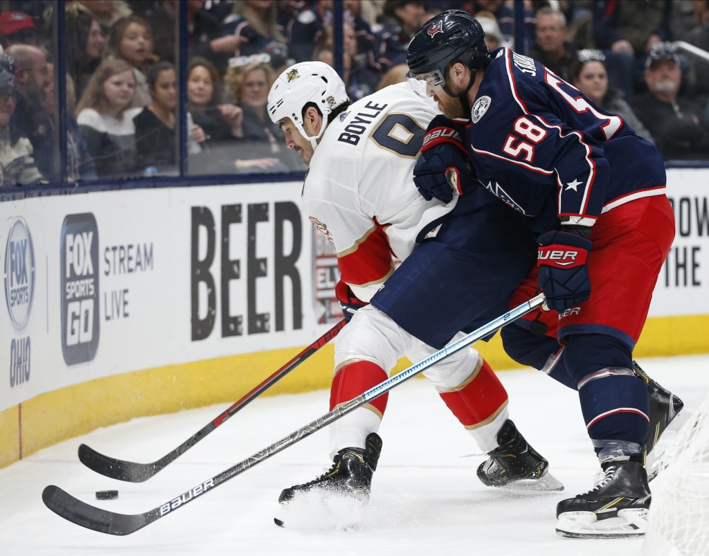 Florida Panthers' Brian Boyle, left, tries to control the puck as Columbus Blue Jackets' David Savard defends during the first period of an NHL hockey...