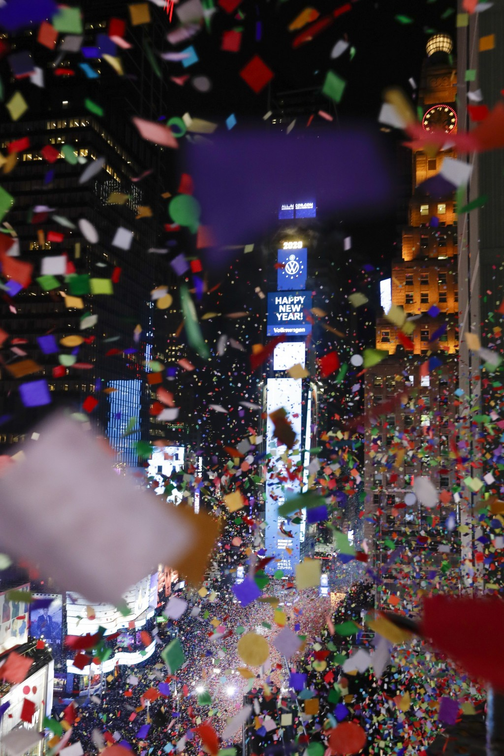 Confetti drops over the crowd as the clock strikes midnight during the New Year's celebration as seen from the New York Marriott Marquis in New York's...