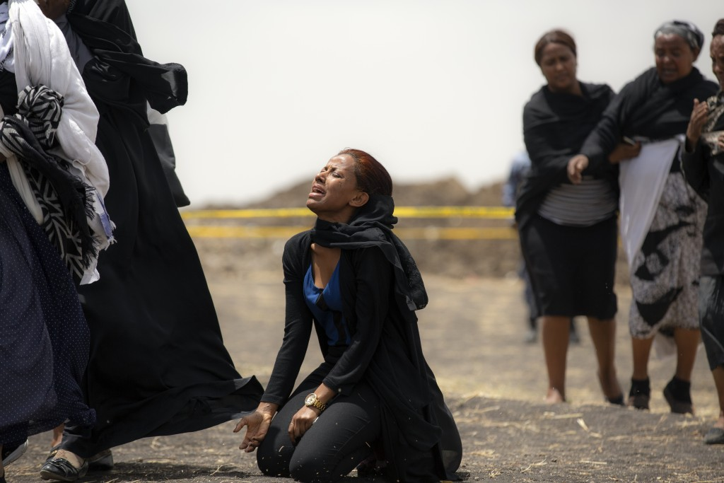 FILE - In this March 14, 2019 file photo, relatives of crash victims mourn at the scene where an Ethiopian Airlines Boeing 737 Max 8 passenger jet cra...