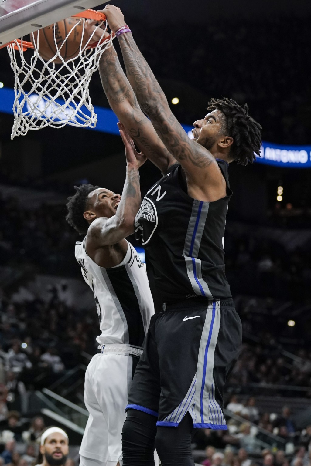 Golden State Warriors' Marquese Chriss, right, dunks against San Antonio Spurs' Dejounte Murray during the first half of an NBA basketball game, Tuesd...