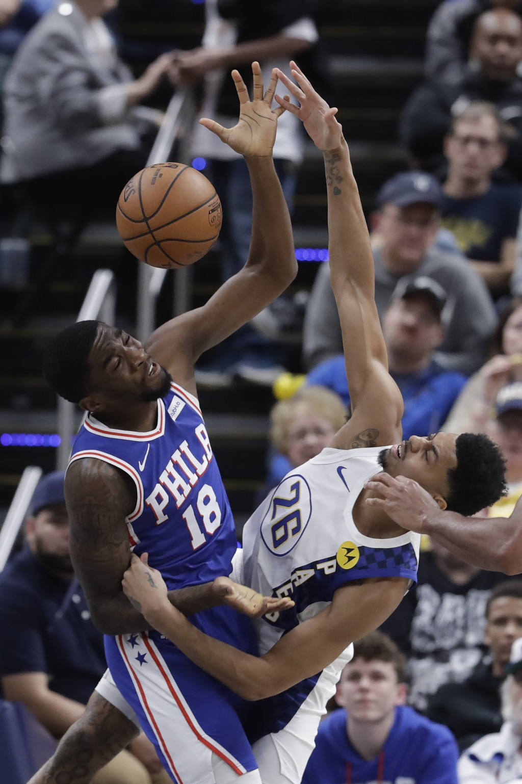Philadelphia 76ers' Shake Milton (18) and Indiana Pacers' Jeremy Lamb (26) battle for a rebound during the second half of an NBA basketball game, Tues...