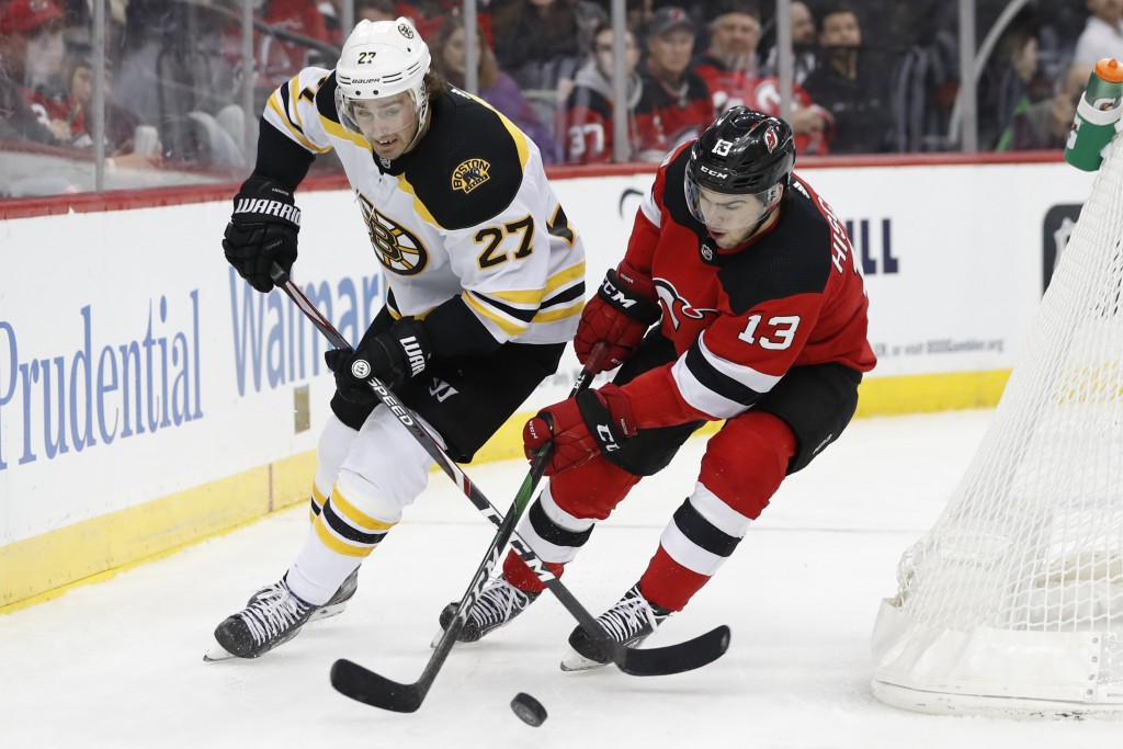 New Jersey Devils center Nico Hischier (13) battles for the puck with Boston Bruins defenseman John Moore (27) during the second period of an NHL hock...