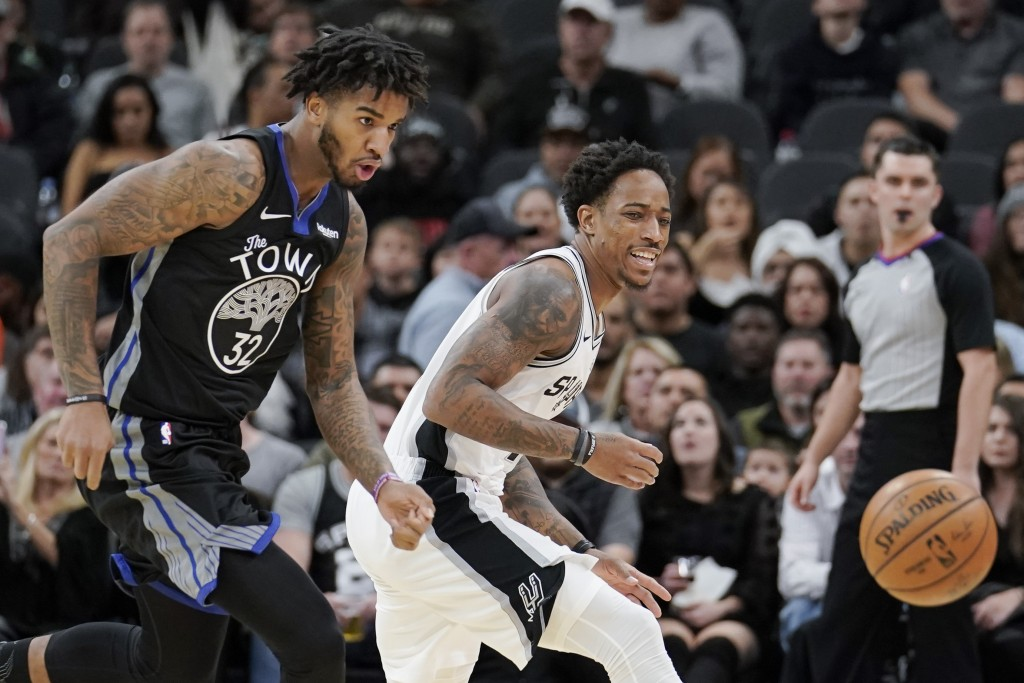 San Antonio Spurs' DeMar DeRozan, right, and Golden State Warriors' Marquese Chriss chase the ball during the first half of an NBA basketball game, Tu...