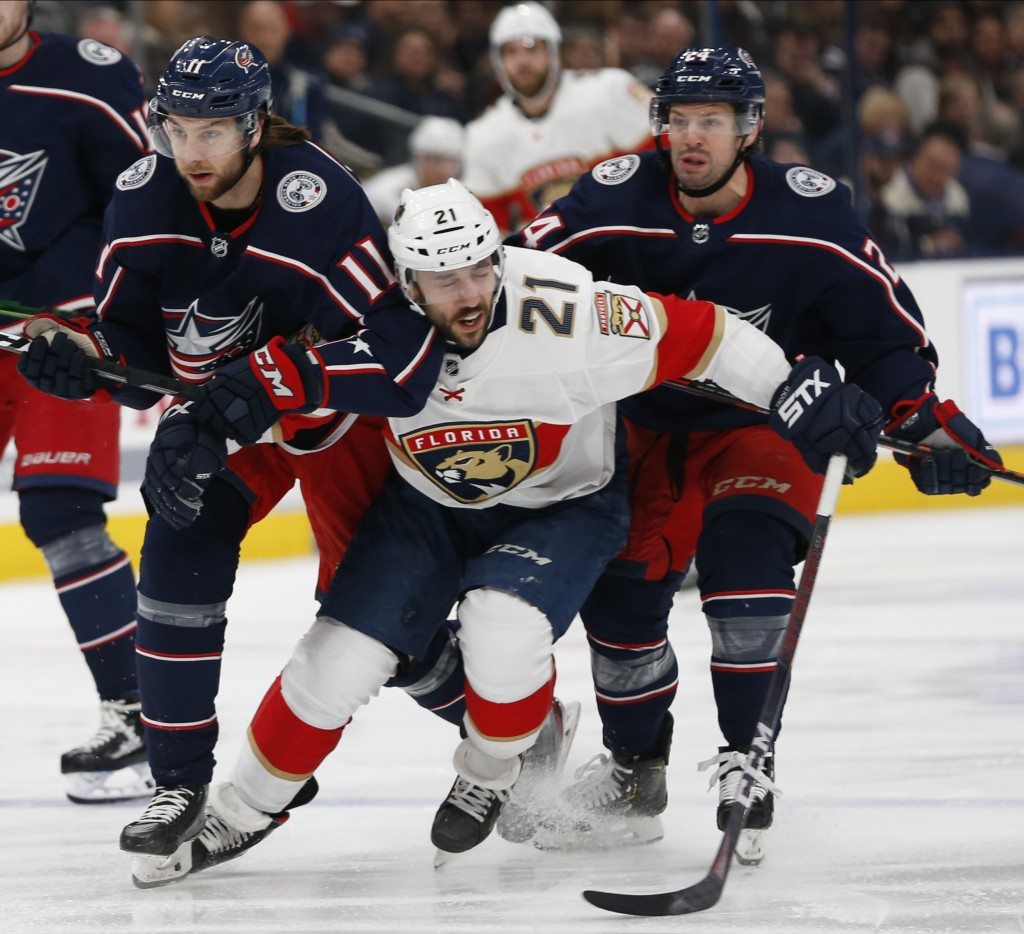Florida Panthers' Vincent Trocheck, center, tries to skate between Columbus Blue Jackets' Kevin Stenlund, left, of Sweden, and Nathan Gerbe during the...