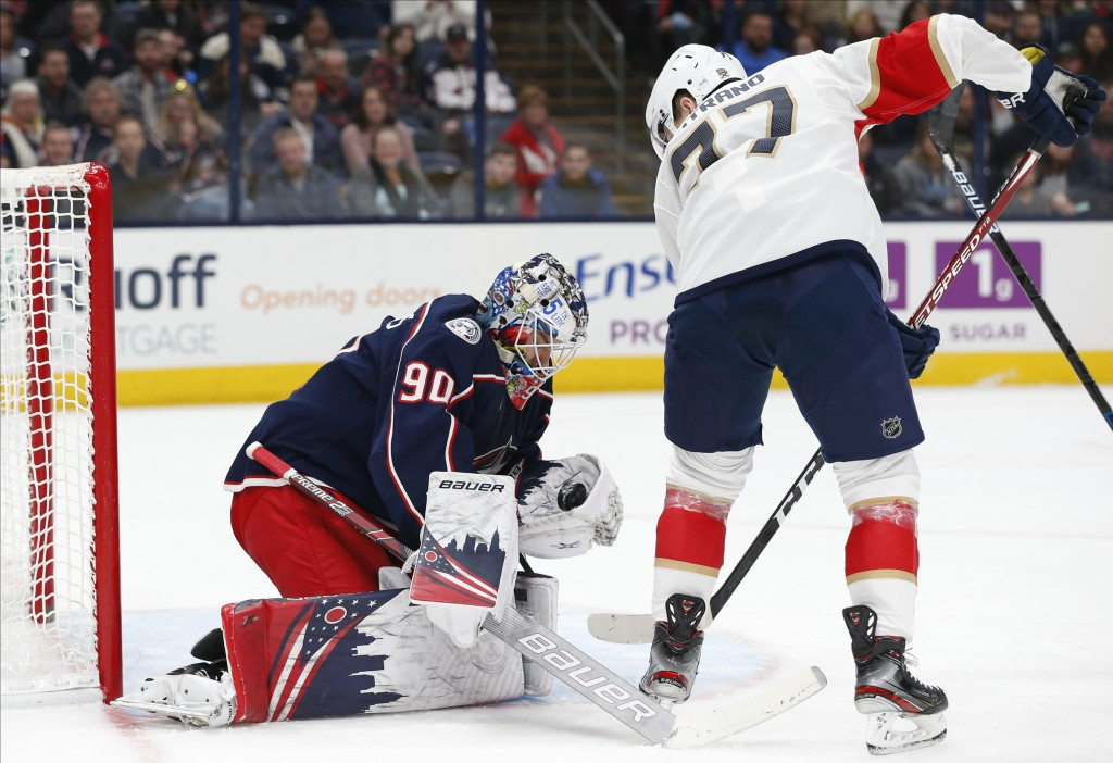 Columbus Blue Jackets' Elvis Merzlikins, left, of Latvia, makes a save against Florida Panthers' Frank Vatrano during the first period of an NHL hocke...