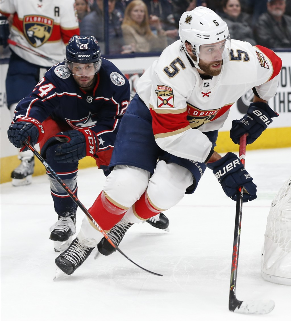 Columbus Blue Jackets' Nathan Gerbe, left, tries to stop Florida Panthers' Aaron Ekblad from passing the puck during the second period of an NHL hocke...