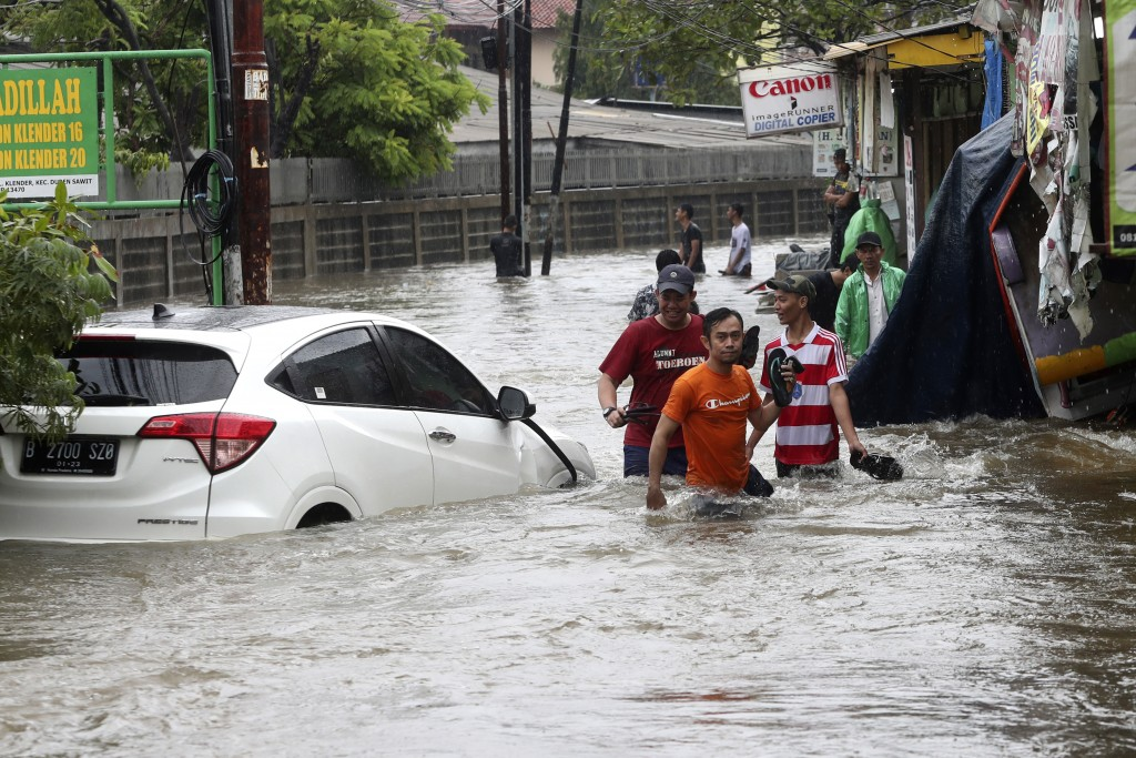 Indonesian people wade through floodwaters in Jakarta, Indonesia, Wednesday, Jan. 1, 2020. Severe flooding hit Indonesia's capital just after resident...