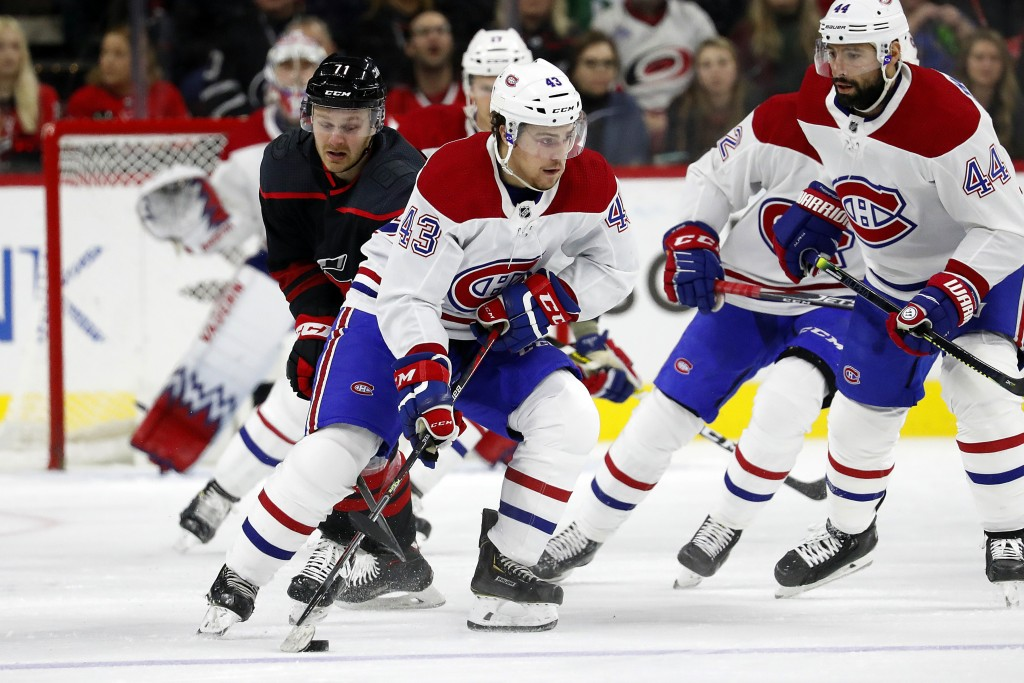 Montreal Canadiens' Jordan Weal (43) moves the puck away from Carolina Hurricanes' Lucas Wallmark (71), of Sweden, during the first period of an NHL h...