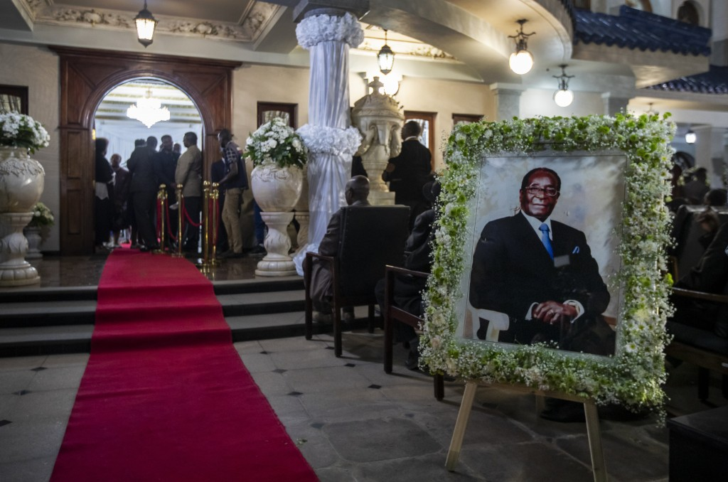 FILE - In this Wednesday, Sept. 11, 2019 file photo, a portrait of former president Robert Mugabe stands outside the room where his body lies in state...