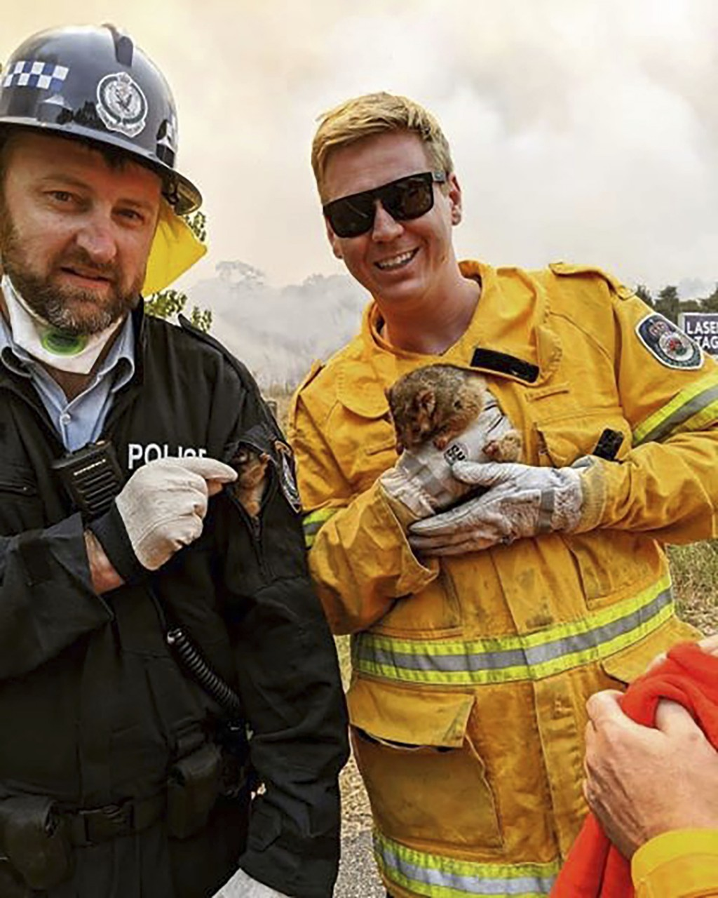 In this image dated Dec. 31, 2019, and provided by NSW Rural Fire Service via their twitter account, firefighter and police officer hold a possum and ...