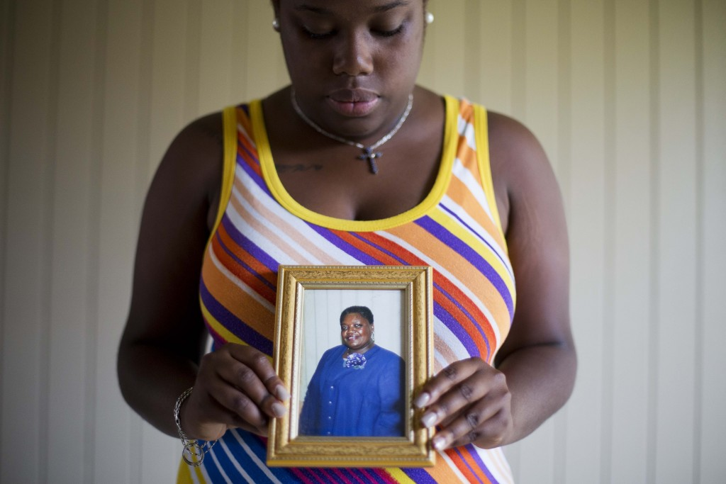 FILE - In this June 19, 2015 file photo, Najee Washington holds a photo of her grandmother Ethel Lance, one of the nine people killed in a shooting at...