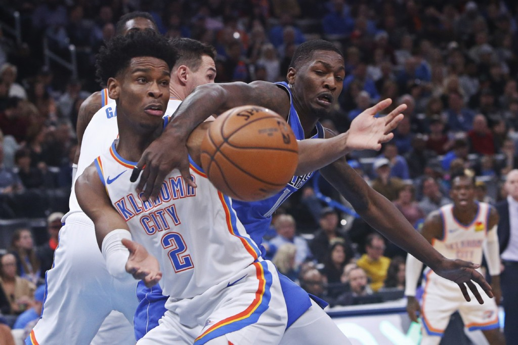 Oklahoma City Thunder guard Shai Gilgeous-Alexander (2) and Dallas Mavericks forward Dorian Finney-Smith, right, reach for the ball during the first h...