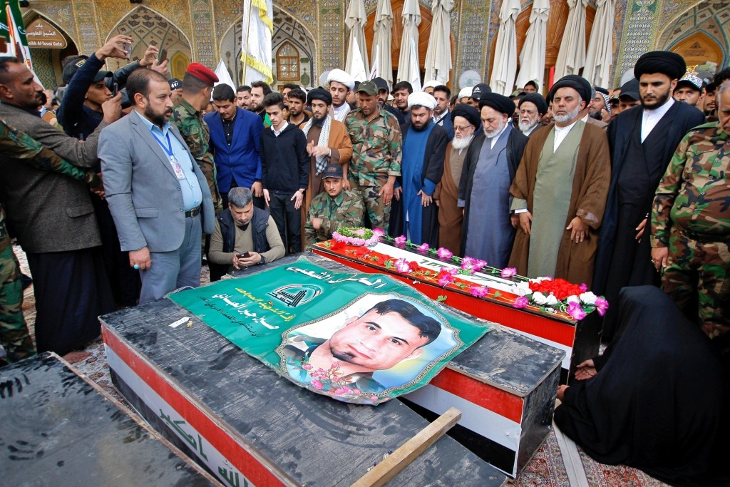 Mourners pray by coffins of Iran-backed Popular Mobilization fighters killed in a U.S. airstrike in Qaim, during their funeral in Najaf, Iraq, Tuesday...