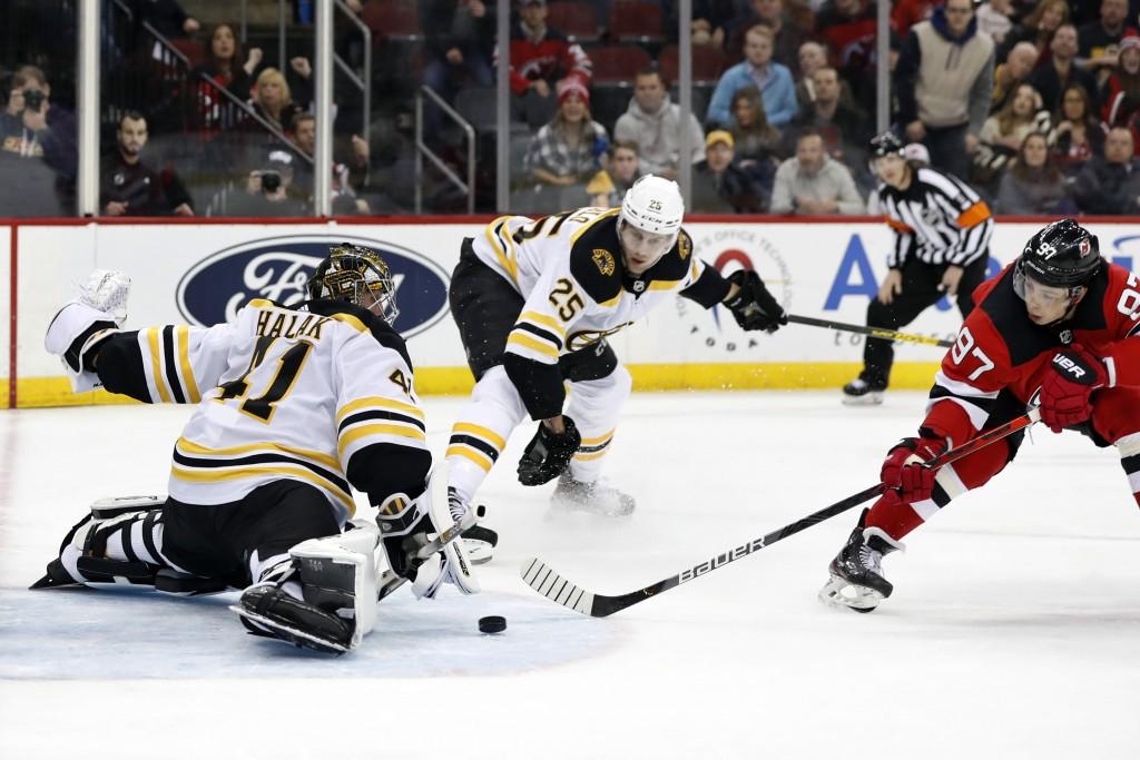 New Jersey Devils left wing Nikita Gusev (97) tries to get a shot past Boston Bruins goaltender Jaroslav Halak (41) as Bruins defenseman Brandon Carlo...