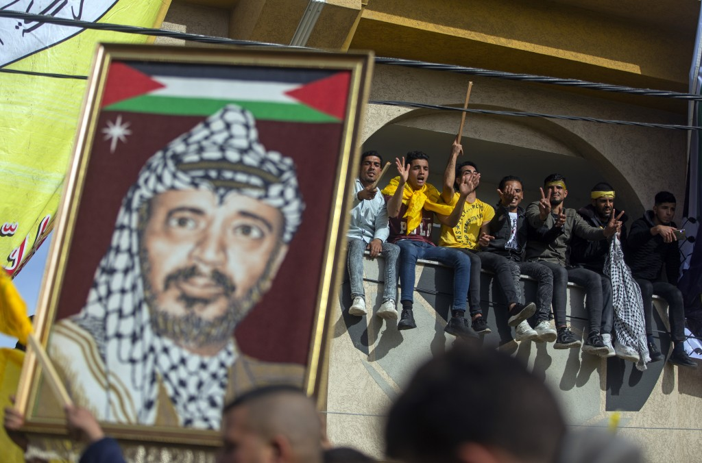 A man carries a picture of the late Palestinian leader, Yasser Arafat, during a rally marking the 55th anniversary of the Fatah movement founding, a  ...